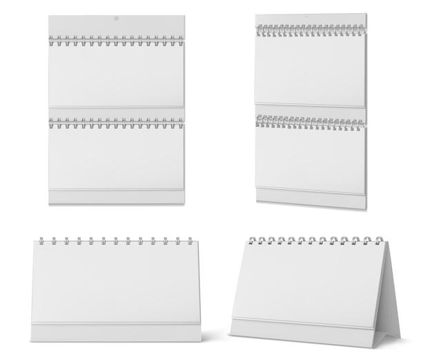 白い背景で隔離スパイラルと空白のページを持つデスクトップと壁掛けカレンダー。テーブルの上に立っているか、壁に掛かっているホワイトペーパーカレンダー、オフィスプランナーまたはメモ帳のリアルなモックアップ