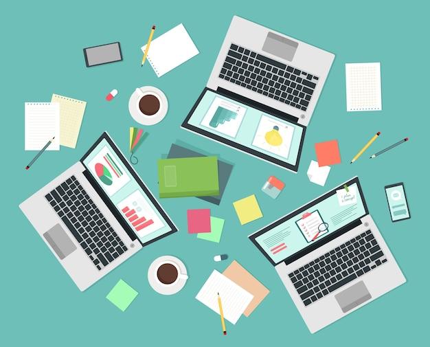 Рабочий стол с ноутбуками, вид сверху. бизнес-концепция совместной работы. работа коллектива и бизнесменов. иллюстрация в плоском стиле.