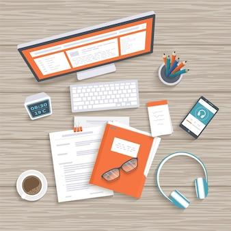 Desktop with monitor keyboard documents folder headphones phone clock notebook coffee