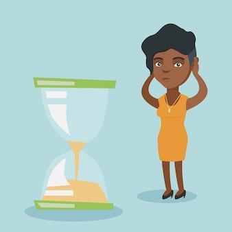 Отчаянные деловая женщина, глядя на песочные часы.