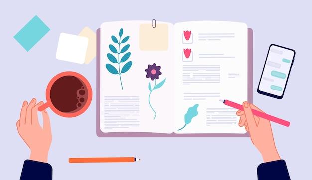 日記を書く。スケッチブックで描く人。ペンとコーヒーカップでトップビューの手。朝の夕方リラックス、思い出作り