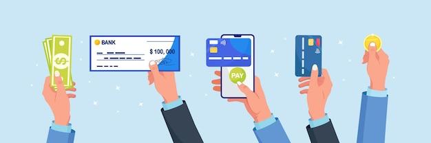 다양한 유형의 비즈니스 지불. 사업가는 직불 카드나 신용 카드, 서명이 있는 은행 수표, 달러 돈, 동전을 보유하고 있습니다. 손에 모바일 뱅킹 앱이 있는 전화. 온라인 무현금 결제 또는 현금