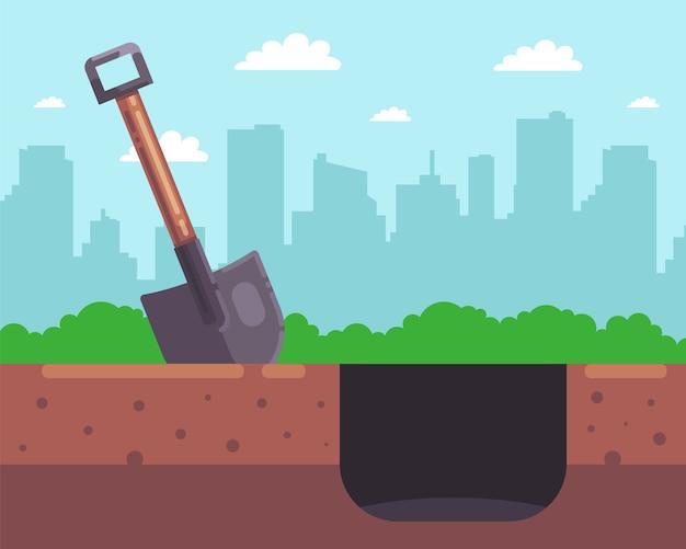 街の背景に木製のシャベルで深い穴を掘ります。