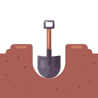 シャベルで地面に穴を掘る