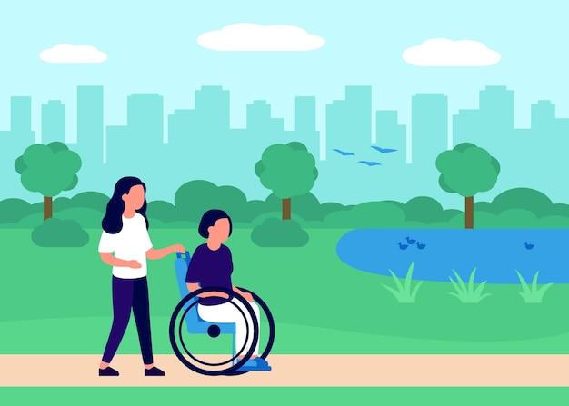 都市公園のハンディキャップリハビリテーションでボランティアの助けを借りて車椅子で歩く障害のある女性