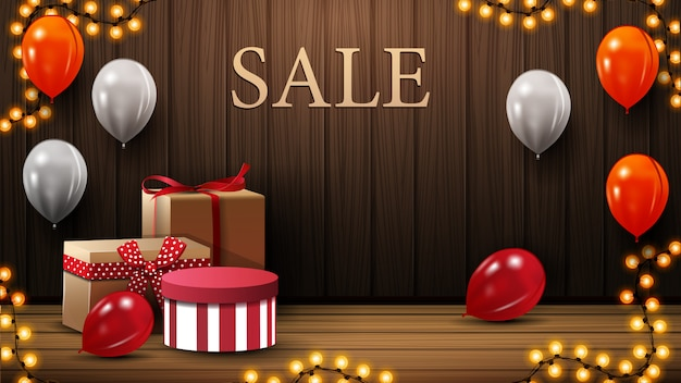 Discount banner with gift boxes, white, orange and red balloons in room on gender near a wooden wall.