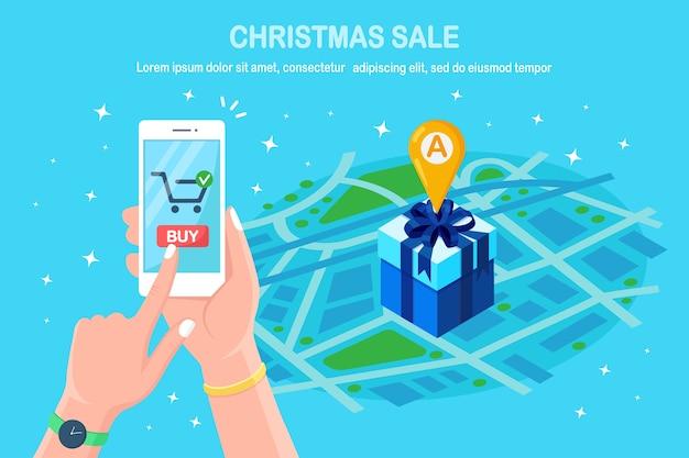 割引クリスマスセール、オンラインショッピングのコンセプト。ピン、地図上のマーカー付きの3dアイソメトリックギフトボックス。携帯電話、アプリケーションを手にしたスマートフォン