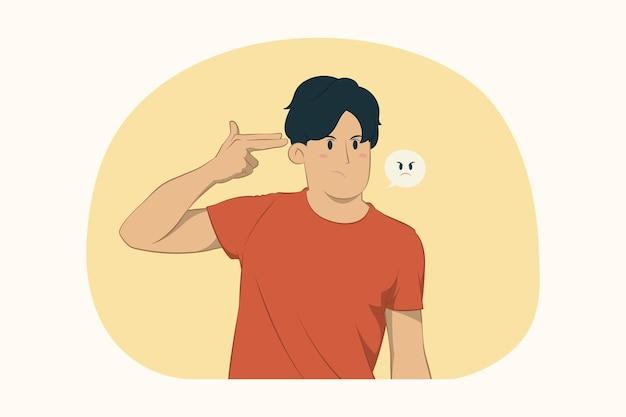 Недовольный молодой человек указывает пальцем на голову, как будто он собирается застрелиться