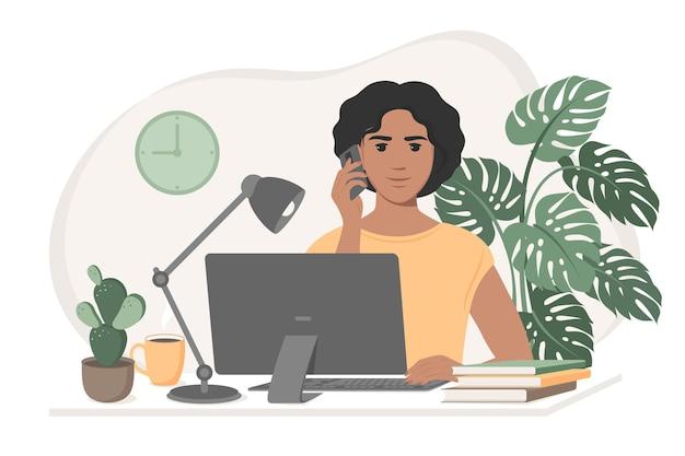 遠隔作業電話に応答するコンピューターを持って机に座っている女性