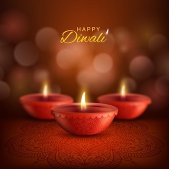 インドのヒンドゥー教の光の祭典、ディーパバリのディワリディヤランプ。火の炎とペイズリー柄のランゴーリー装飾が施された赤い粘土の石油ランプ、ハッピーディワリのグリーティングカード