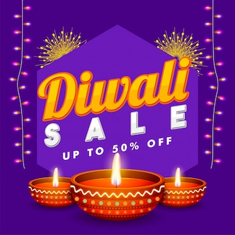 Diwali sale flat 50%  banner with illuminated oil lamps.