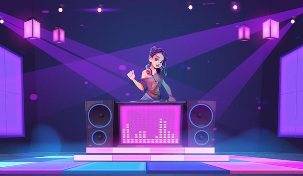 Djの女の子がヘッドフォンでナイトクラブの若い女性のディスクジョッキーのターンテーブルに立つ