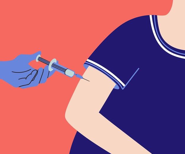 注射器を持った医師の手が患者の肩にワクチンを注射する手術用手袋をはめた手