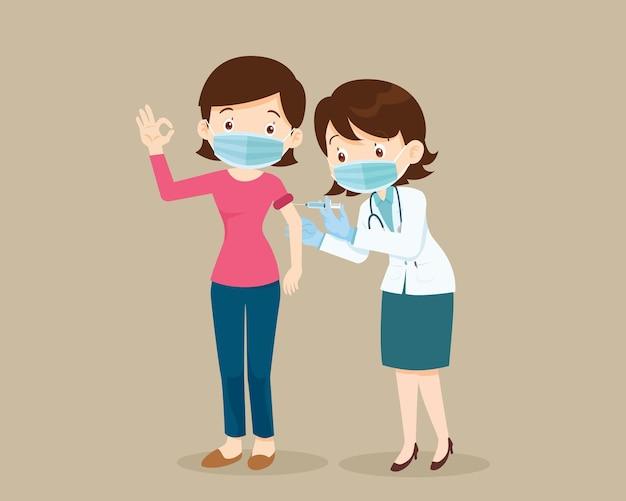 Доктор вводит вакцину против коронавируса covid19 для женщины, показывающей хороший жест