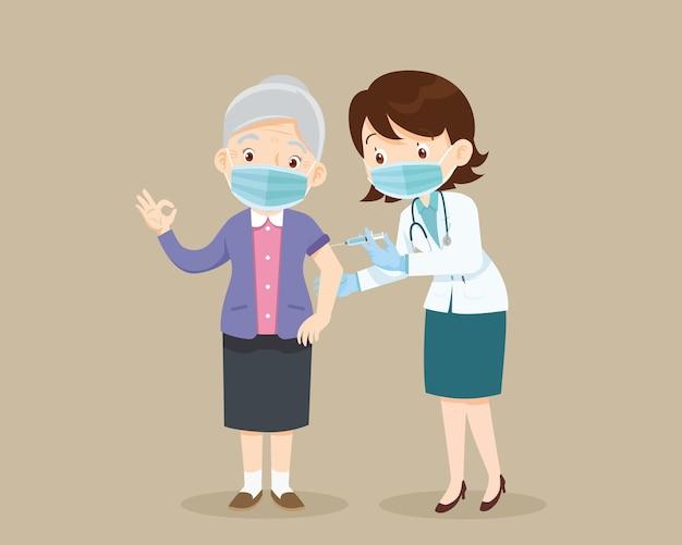 Доктор вводит вакцину от коронавируса пожилой женщине старший в маске показывает жест