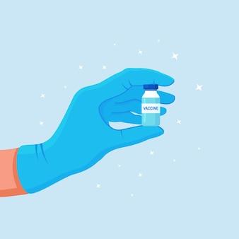 의사, 간호사는 유리병, 앰플, 코로나바이러스 백신이 든 병을 들고 파란색 의료 장갑을 끼고 있습니다.