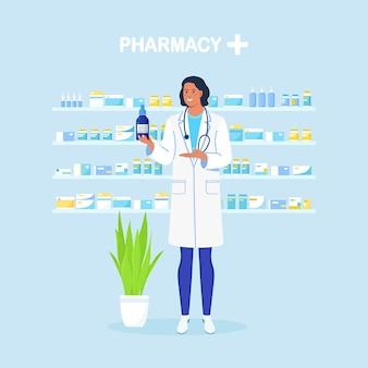Врач-фармацевт, стоя и держа лекарство. полки с таблетками и бутылками на фоне. покупки в аптеке