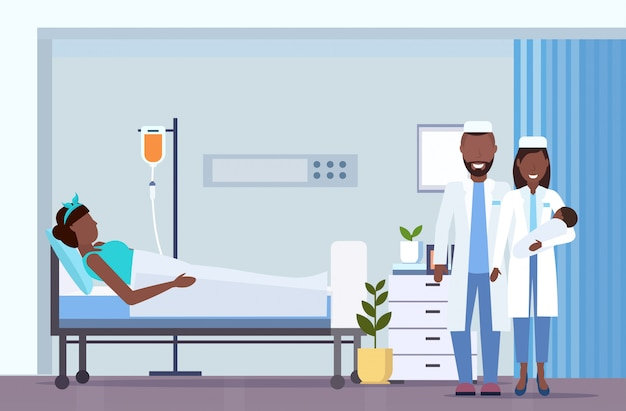 Doctor with nurse holding newborn baby near   mother lying in bed with dropper childbirth concept modern maternity ward post natal department room interior horizontal full length