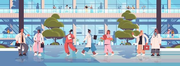 의사 유니폼 서 함께 혼합 인종 의료 노동자 팀 회의 의료 의학 개념 병원 건물 외관 수평 동안 논의