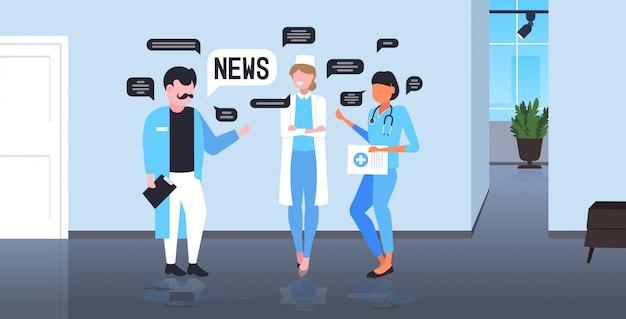 Команда врачей болтает во время встречи, обсуждая концепцию коммуникации пузыря ежедневного чата новостей. интерьер больницы в полный рост