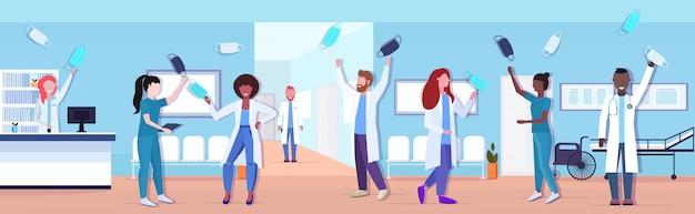 코로나 바이러스 전염병 검역소 covid-19에 승리를 축하하는 얼굴 마스크를 벗고 의사 팀