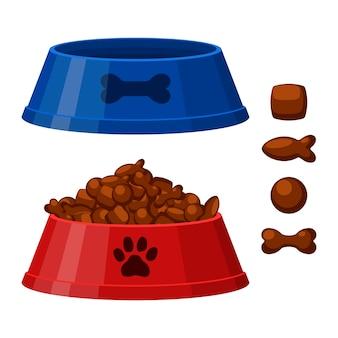 개 또는 고양이 건조 식품 그릇. 뼈와 생선 모양의 칩. 건조 식품과 함께 빨간색과 파란색 애완 동물 그릇.