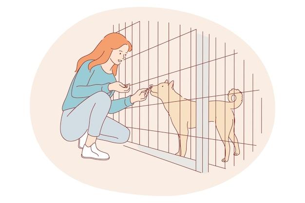 避難所からの犬、ボランティア、動物の概念を支援します。座っている若い幸せな女の子の漫画のキャラクター
