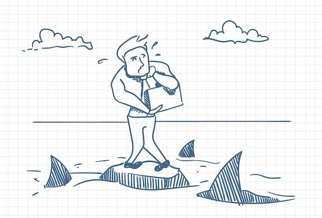Бизнесмен doodle стоя на скале с акулами вокруг концепции опасности и кризиса
