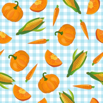 Drawn pumpkin carrot and corn symbols vegetable pattern on light blue checkered tablecloth