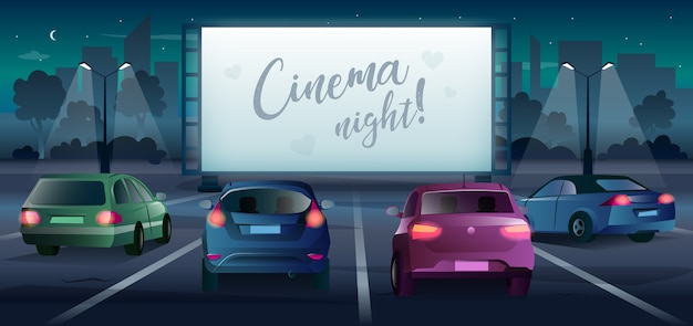 Drive in movie theater with large screen and cars