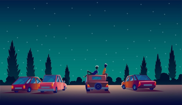 Drive in theater with automobiles stand in open air parking at night