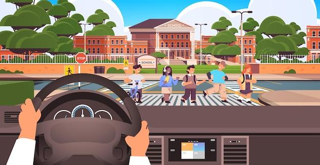 Водитель держит руль и ждет школьников, переходящих дорогу на пешеходном переходе возле здания школы безопасность дорожного движения