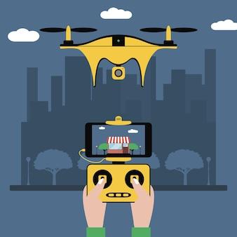 드론 및 원격 제어 손은 도시를 비행하는 쿼드콥터에 화면이 있는 라디오 컨트롤러를 들고 있습니다.