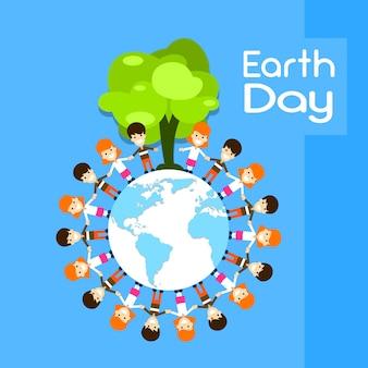 Earth day children group stand around globe