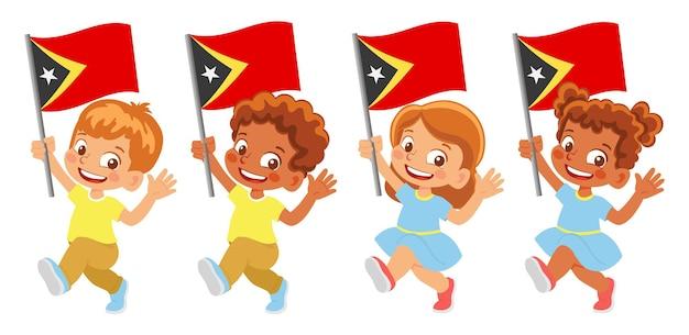 Флаг восточного тимора в руке. дети держат флаг. государственный флаг восточного тимора