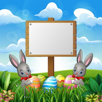 Easter bunnies with eggs and blank sign on the field