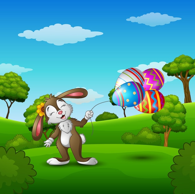 Easter bunny holding easter eggs balloons in the park