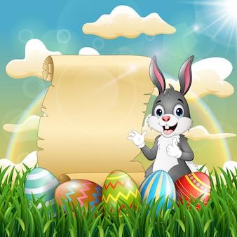 スクロール紙とイースターエッグの近くのイースターのウサギ