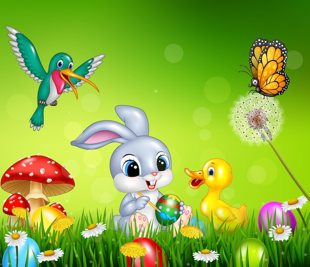 Пасхальный кролик с украшенными пасхальными яйцами в поле