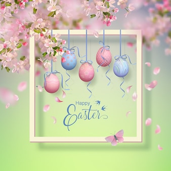 Easter decorative frame with blooming spring branches, hanging painted eggs and falling petals