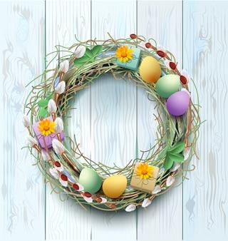 イースターリース装飾。柳の枝と青い木製の背景に着色された卵