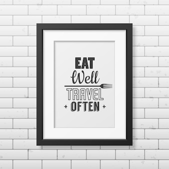 Eat well, travel often - typographical quote in realistic square black frame on the brick wall.