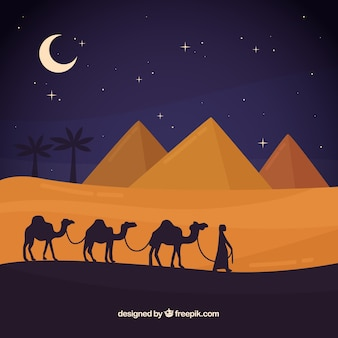 ピラミッドとキャラバンを持つエジプトの夜の風景のコンセプト