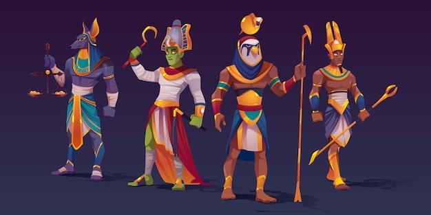 Египетские боги анубис, ра, амон и осирис. персонажи божеств древнего египта в одежде фараона, держащей божественные атрибуты силы в виде чешуи с золотыми монетами и посохами, векторная иллюстрация мультяшныйа