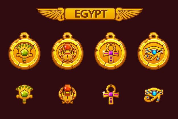 スカラベ、目、花、クロスを持つエジプトのお守り。古びたエジプトの黄金のお守りと色の宝石。