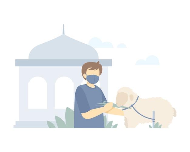 イスラム教徒の男性とイードアル犠牲の背景はモスクの図の前で羊に餌をやる