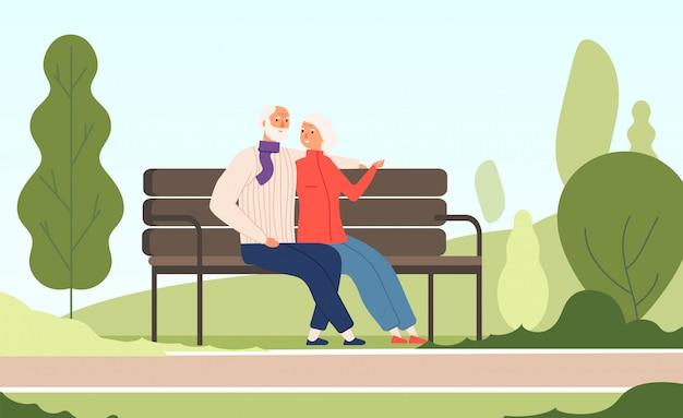 老夫婦公園。夏の自然都市公園のコンセプトで古い家族のベンチに座っている高齢者の幸せな祖父祖母