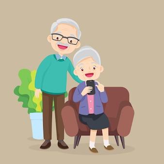 ソファに座って、リビングルームで電話を見ている老人と女性