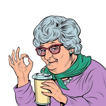 Пожилая женщина бабушка пьет кока-колу, хорошо жест