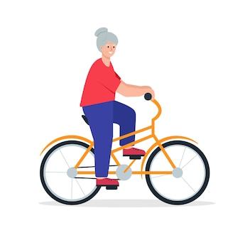 Bycicleの上の年配の女性笑顔の引退した女性の乗車自転車高齢者のアクティブなライフスタイルの概念